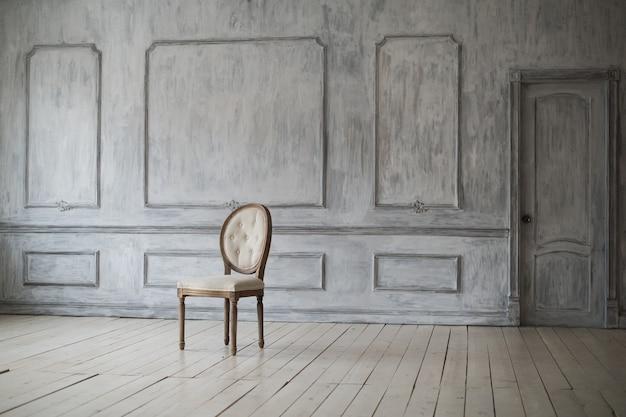 Silla vintage blanca de pie delante de una pared de luz con molduras en el piso de parquet de madera.