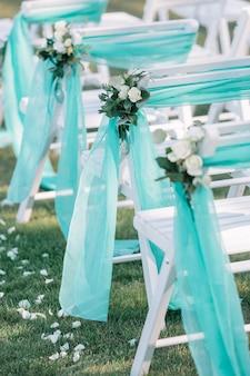 Sillas blancas para invitados decoradas con tela de menta