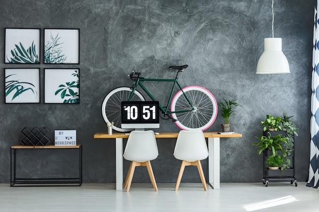 Sillas blancas en la mesa con monitor de computadora y bicicleta en un interior moderno con carteles brillantes en la pared