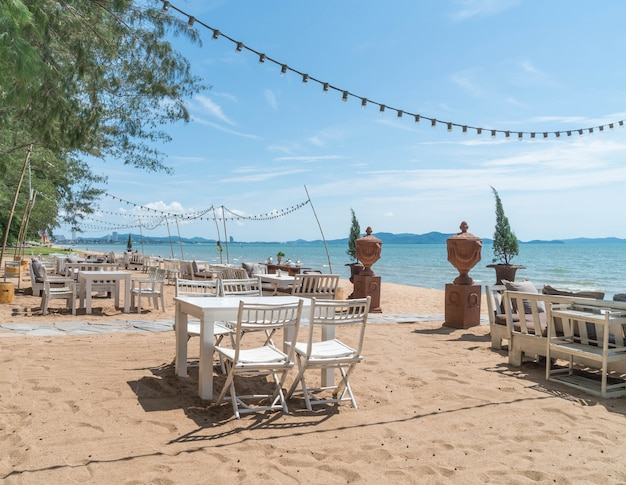 Sillas blancas y mesa en la playa con una vista del océano azul y cielo claro