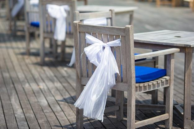 Sillas de boda decoradas con lazos blancos en café al aire libre