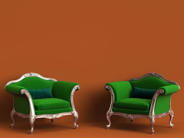 Sillas clásicas en verde y oro sobre pared naranja con espacio de copia