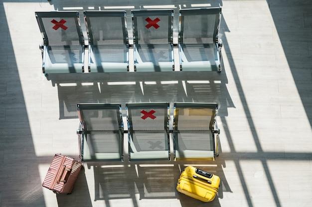 Sillas de espera sin nadie en la terminal del aeropuerto durante la pandemia de covid-19 con letreros de distanciamiento social en las sillas