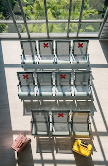 Sillas de espera vacías de la terminal del aeropuerto durante la pandemia de covid-19 con carteles de distanciamiento social en sillas con maletas o equipaje