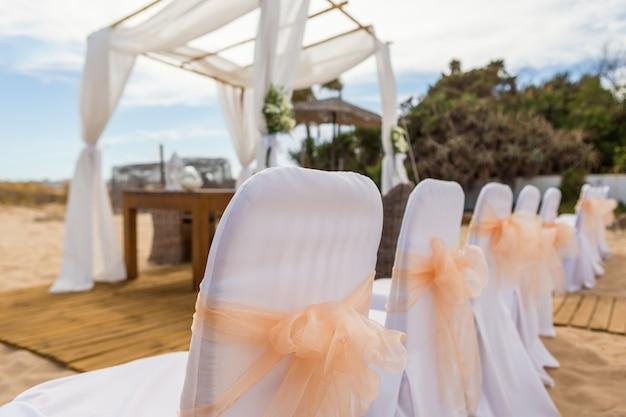 Sillas con lazos en la ceremonia de la boda. de cerca.