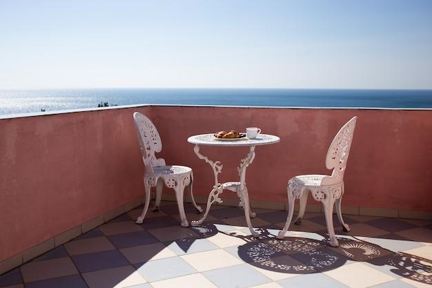 Sillas y una mesa están en el balcón con impresionantes vistas al mar