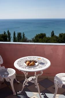 Sillas y una mesa están en la terraza con impresionantes vistas al mar