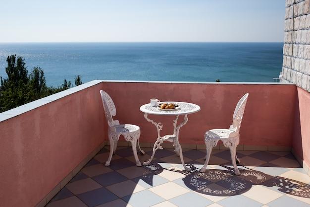 Sillas y una mesa están en la terraza con increíbles vistas al mar