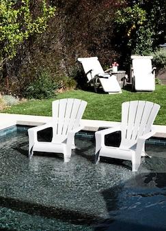 Sillas de plástico blanco en una piscina