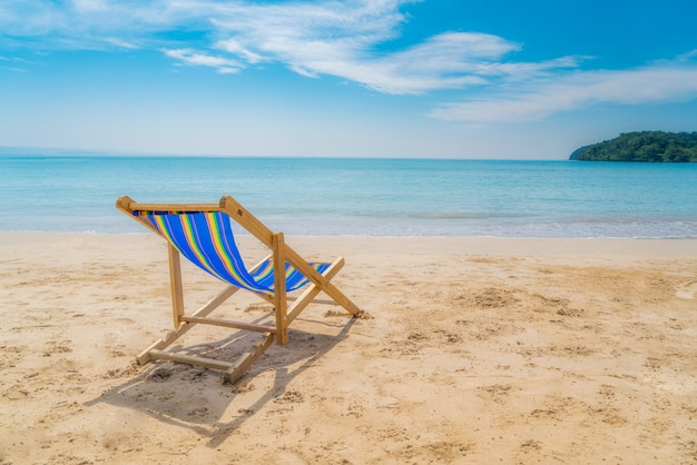 Una sillas de playa en la arena blanca con cielo azul y mar de verano