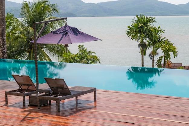 Sillas de playa junto a la piscina con bonitas vistas al mar.