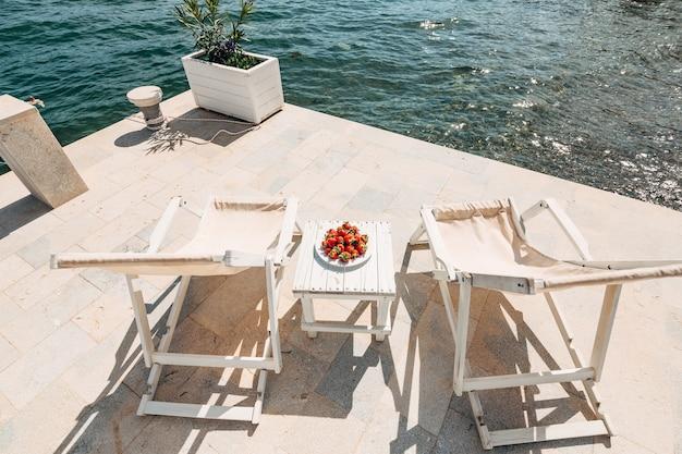Sillas de playa de madera blanca junto al mar