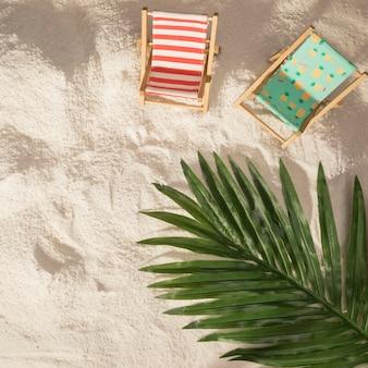 Sillas de playa con palmeras y juguetes.