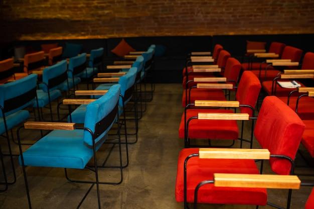 Sillas rojas y azules en el oscuro salón de un pequeño cine.