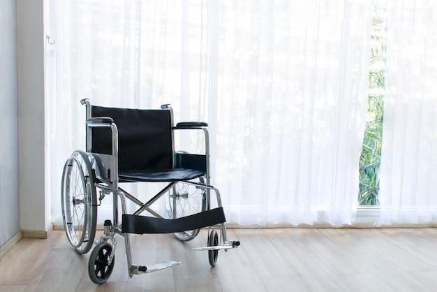 Sillas de ruedas que esperan servicios en la sala de hospital con luz solar cerca de la ventana.