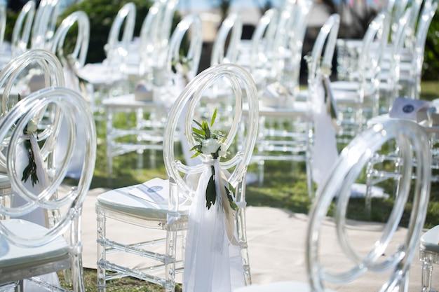 Sillas transparentes blancas en la ceremonia de la boda.