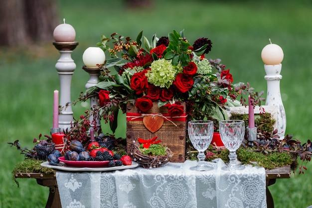 Sillas y velas, flores, platos de cerámica con frutas, de pie sobre el mantel de encaje y musgo.