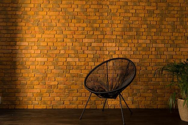 Sillón cerca de la pared de ladrillo amarillo y palmera en una maceta