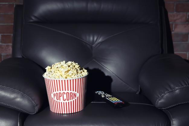 Sillón de cuero con palomitas de maíz y mando a distancia en home cinema