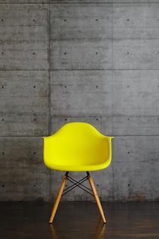 Sillón de diseño moderno de plástico amarillo sobre soportes de madera.