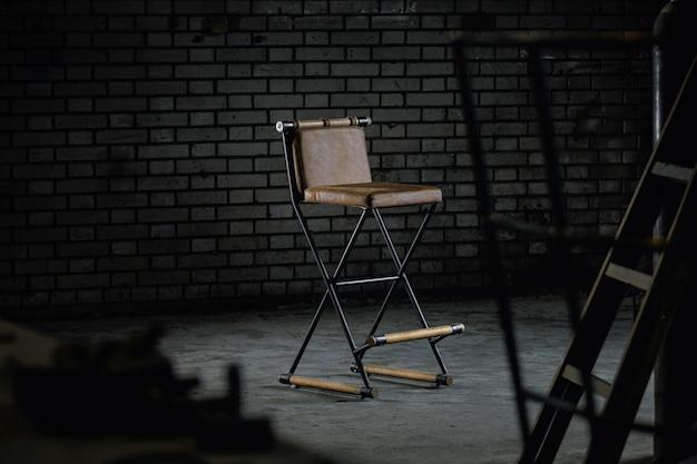 Sillón de peluquero de madera simple en un estudio bajo las luces