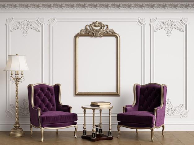 Sillones clásicos en interior clásico con marco clásico vacío en la pared.