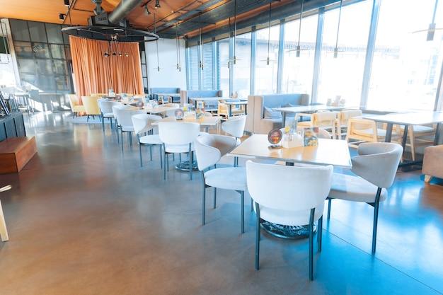 Sillones cómodos sillones cómodos blancos de pie cerca de mesas de madera en un espacioso restaurante