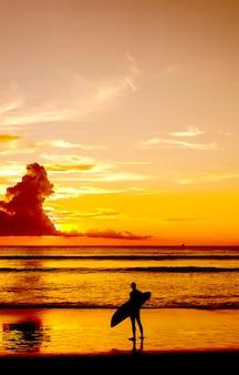 Silueta de algunas personas con tabla de surf en la playa de arena