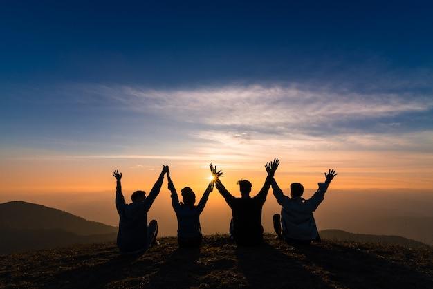 Silueta de amigos agitar las manos y sentarse juntos en la felicidad del atardecer
