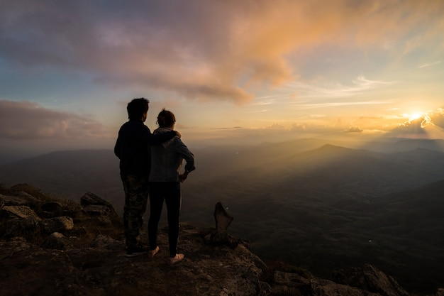 Silueta de amorosa pareja abrazándose en la montaña