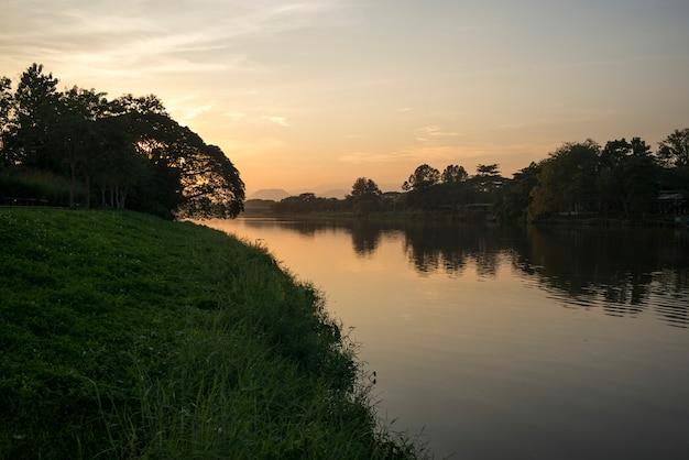 Silueta de árboles en la orilla del río al atardecer, chiang rai, tailandia