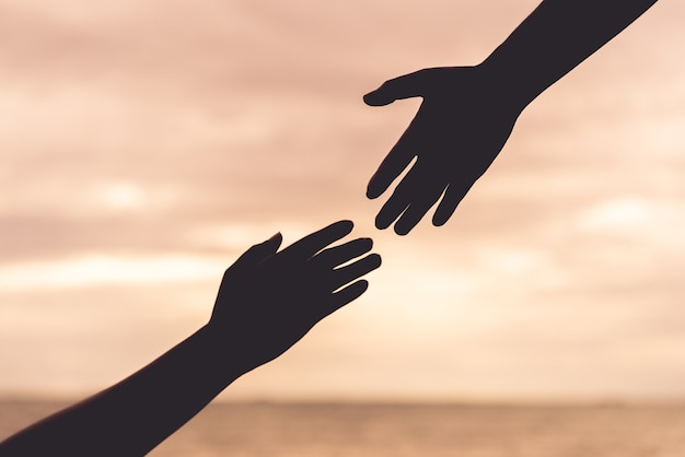 Silueta ayudando a las manos sobre fondo de cielo. concepto de día de la amistad