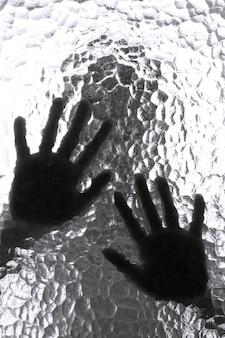Silueta borrosa de una persona y sus manos detrás de la puerta con textura de vidrio