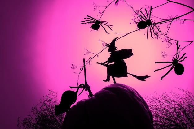 Una silueta de bruja voladora y arañas de papel negro sobre degradado rosa