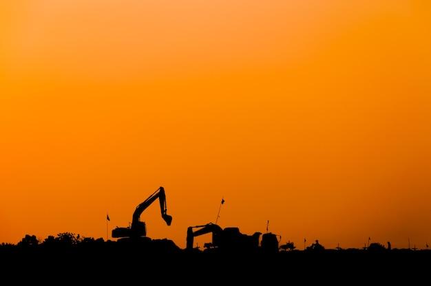 Silueta de cargador de excavadora en el sitio de construcción, silueta retroexcavadora