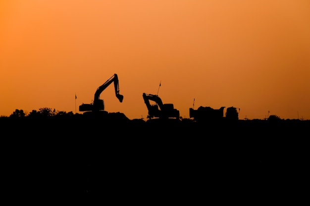Silueta del cargador de excavadora en el sitio de construcción