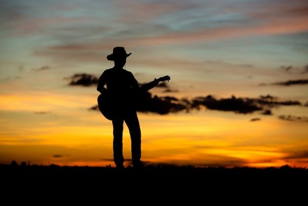 Silueta chica guitarrista en una puesta de sol