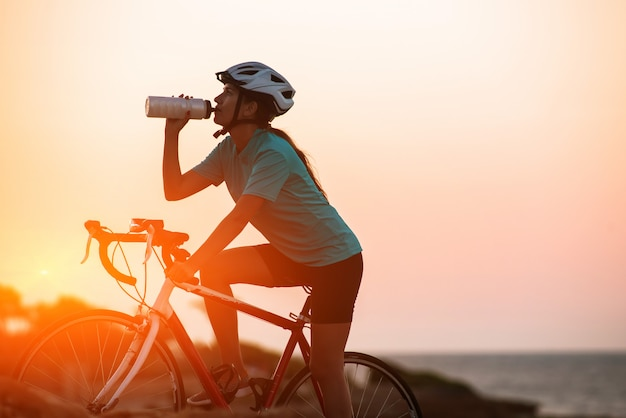 Silueta de ciclista femenina montando bicicleta y dringking agua con mar o
