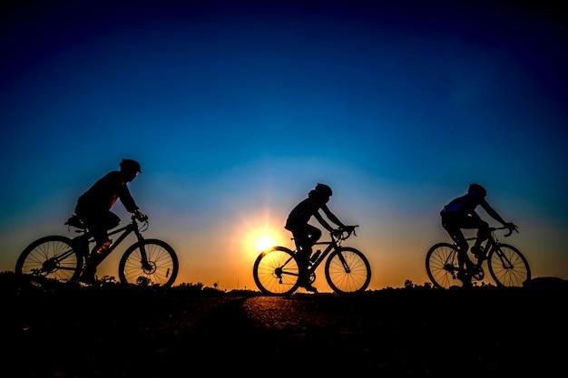 Silueta del ciclista en fondo de la puesta del sol.