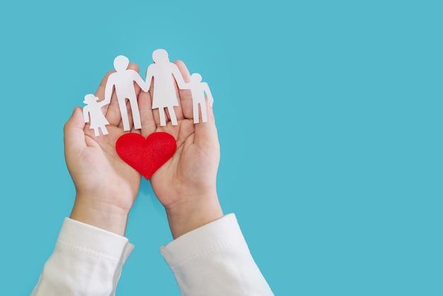 Silueta y corazón en manos de los niños sobre un fondo azul. concepto de amor y bienestar. copie el espacio.