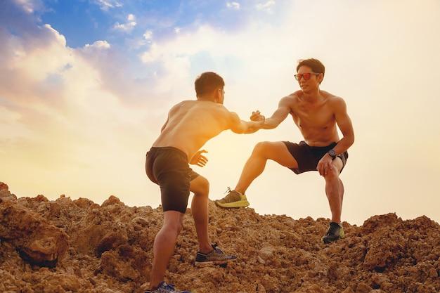 Silueta de corredor de pista con la mano ayudándose mutuamente a subir la cima de una montaña junto con el concepto de ayuda y apoyo de fondo al atardecer