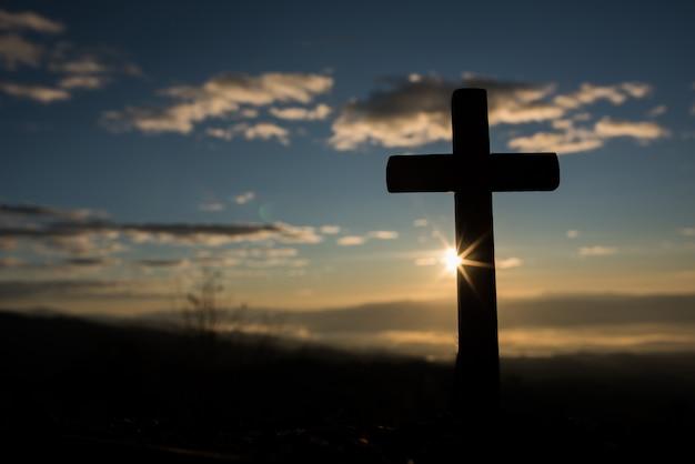 Silueta de cruz católica y amanecer.