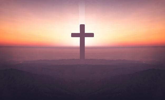 Silueta de la cruz del crucifijo en la montaña en el tiempo de la puesta del sol con el fondo santo y ligero.
