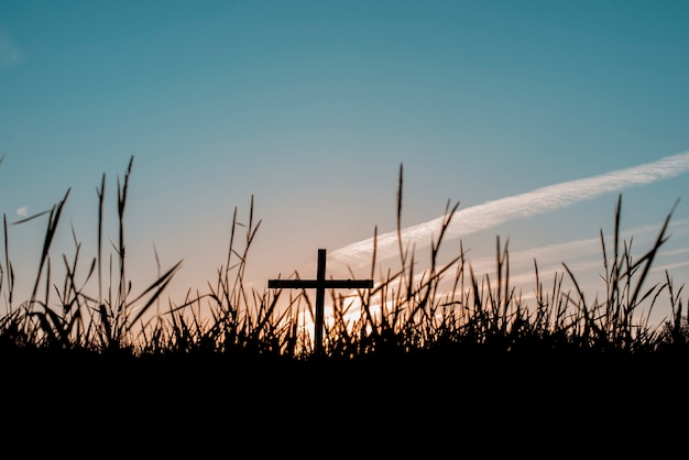 Una silueta de una cruz hecha a mano en el campo.