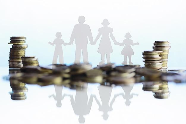 Silueta de cuatro personas y montones de dinero. concepto de familia. presupuesto económico familiar. ahorro por inversión.