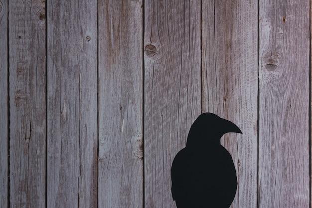 Silueta de cuervo sobre fondo de madera. víspera de todos los santos. copie el espacio.