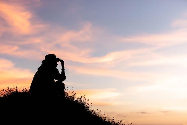 Silueta de mujer está utilizando ideas en la cima de una colina en la puesta de sol