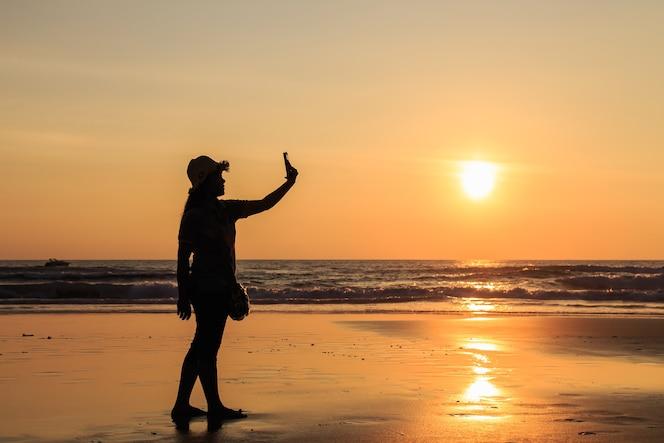Silueta de mujer tailandesa con smartphone en la playa en el atardecer