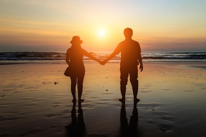 Silueta de pareja tailandesa en la playa en el atardecer