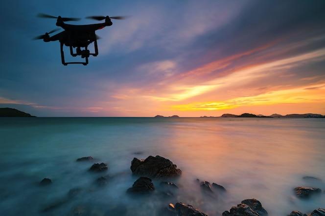 Silueta del drone volando sobre el mar al atardecer